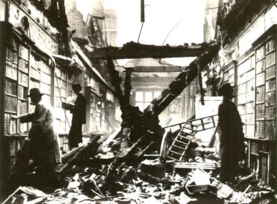 picture of men browsing a library amidst wreckage from recent bombing
